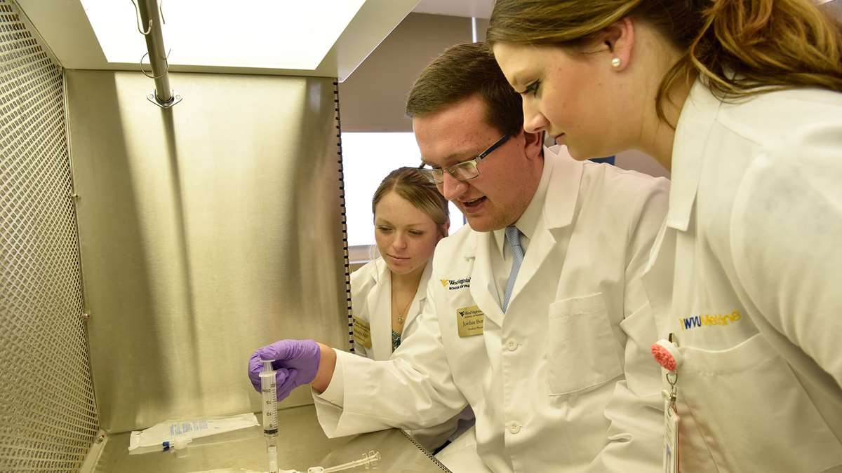 Students in a laboratory watch a professor prepare an IV solution.